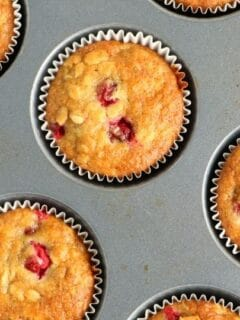 muffin tin with fresh cranberry muffins in it