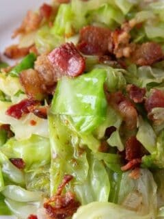 cabbage and bacon dish on a white plate on table