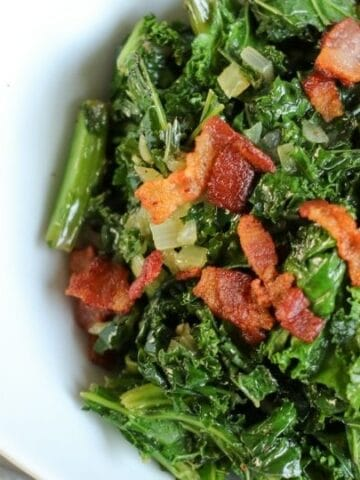 kale and bacon in a white bowl on table