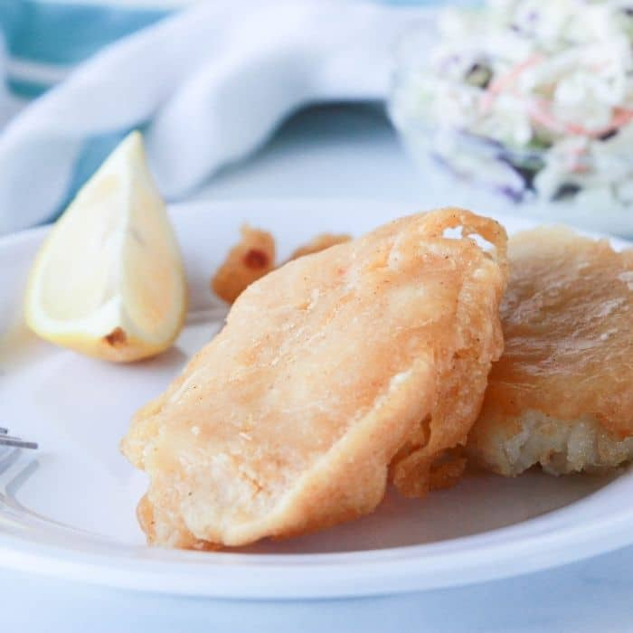 best beer batter fish on plate with lemon wedge