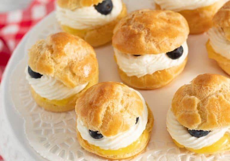 plate of lemon cream puffs with blueberries on it