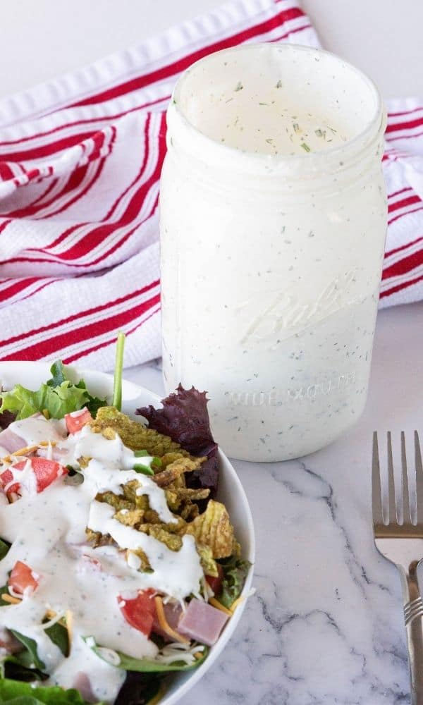salad with dressing and mason jar of dressing beside it on table