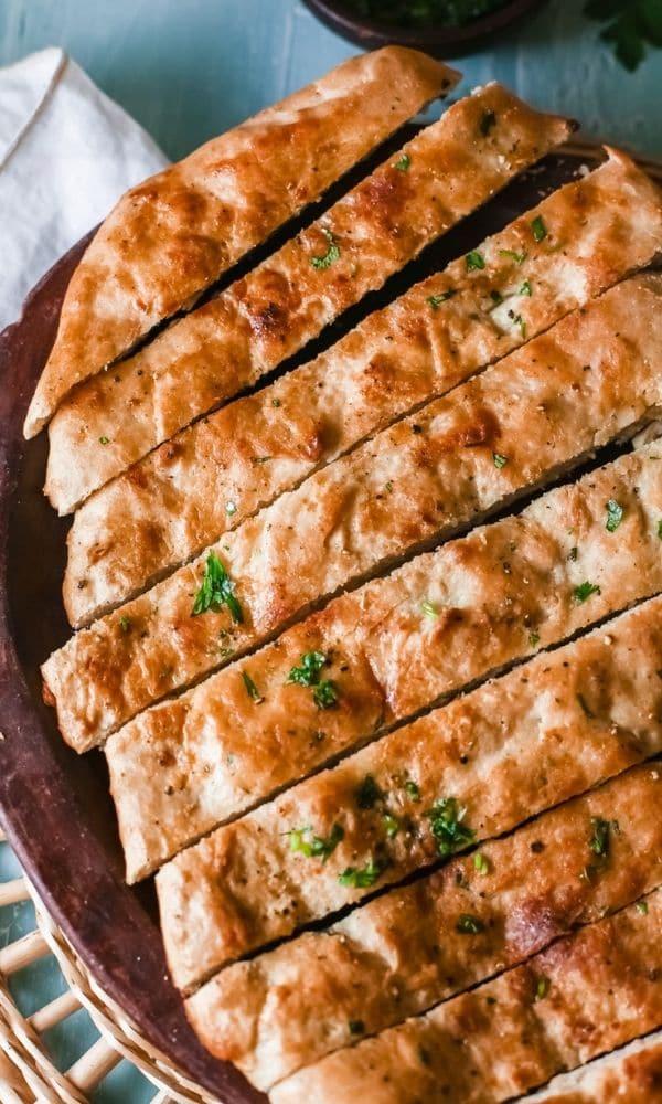 garlic bread on table sliced up on platter