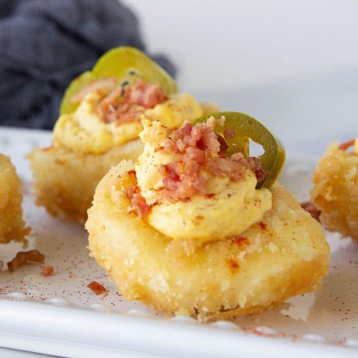 deviled eggs with bacon and jalapeno on platter