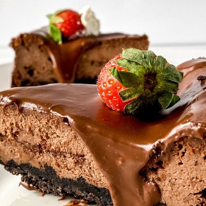 slice of chocolate cheesecake on plate with strawberry on top