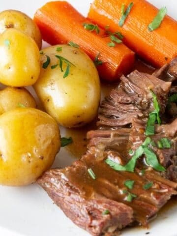 pot roast with gravy and vegetables on a plate
