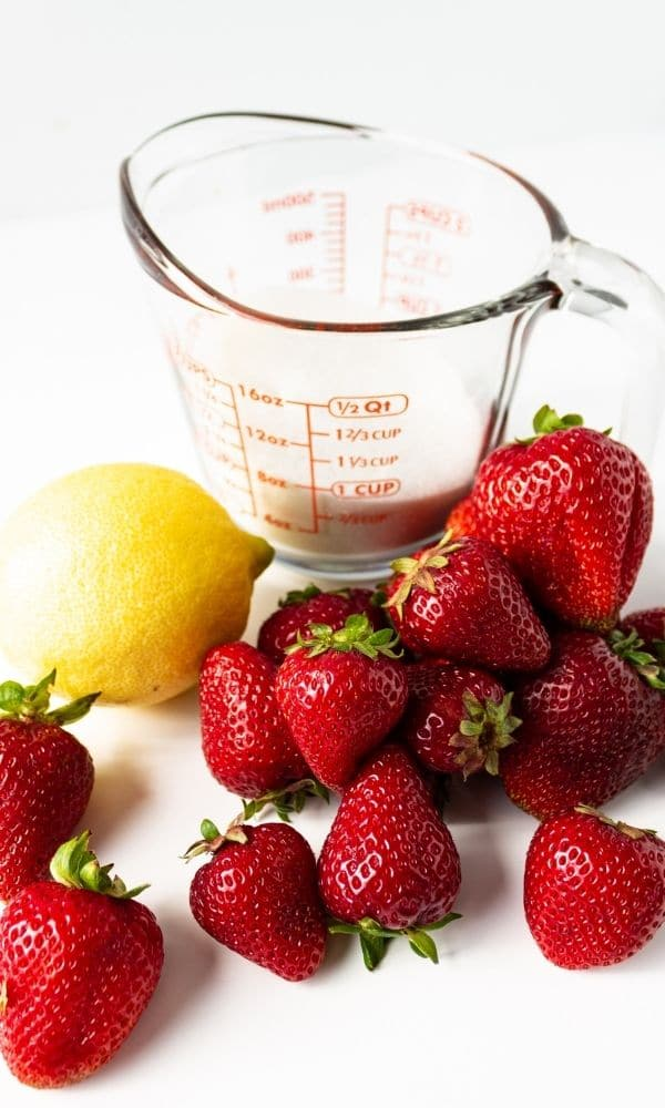 strawberries, lemon and sugar sitting on white table