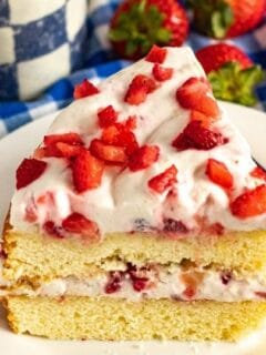 slice of strawberry cake on a plate with blue checkered towel behind it