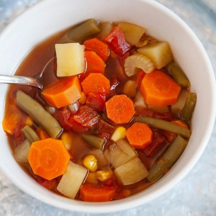 veggie soup in a bowl with spoon in it