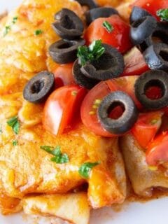 plate of enchiladas topped with tomatoees and black beans
