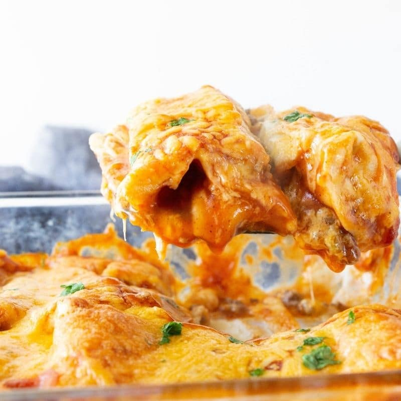 cheesy enchiladas lifting out of pan