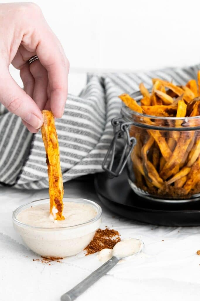 dipping sweet potato fry in homemade sauce on counter