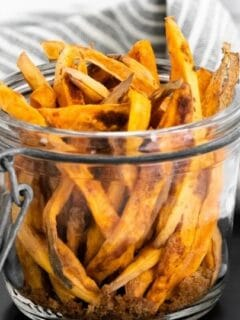 sweet potato fries in a jar with towel behind them