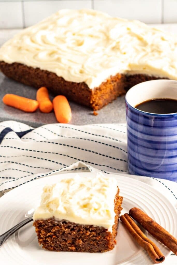 moist carrot cake bars on plate with coffee behind it