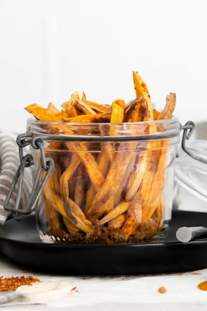 sweet potato fries in a jar on a black platter on table