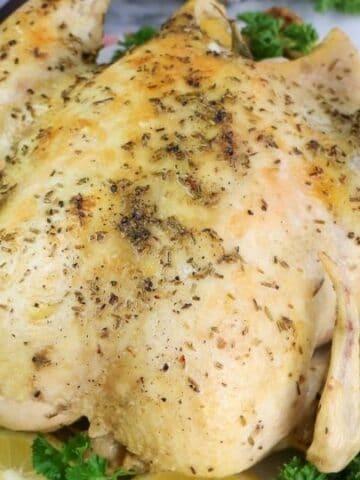 rotisserie chicken on a platter with lemon slices around it