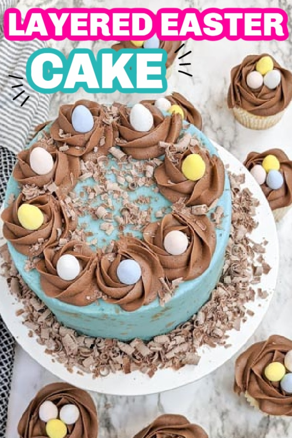egg decorated cake on cake pan with cupcakes around it