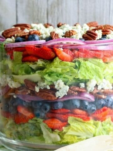 side view of a layered salad in glass bowl
