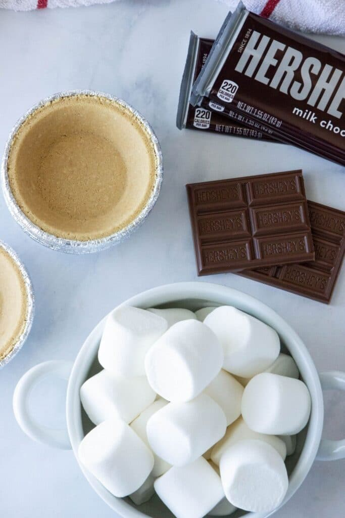 Mini S'mores Pies are so easy to make. An oven-baked s'mores made in single-serve graham cracker pie crusts. Whip up this easy dessert in minutes. Just 3 ingredients needed for this smores recipe. #smores #pies #mini #singleserve #oven #ovenbaked #smoresrecipe #easy #best #homemade #foraparty #3ingredients