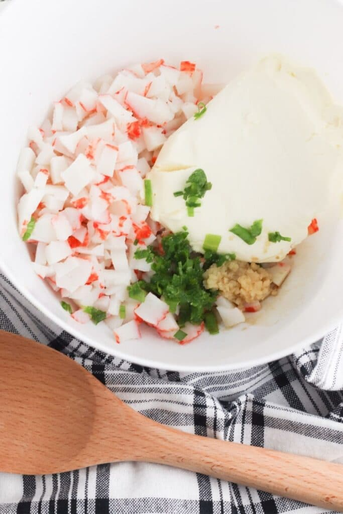 crab rangoon ingredients in a bowl with spoon by it