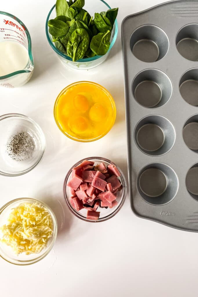 ingredients for egg spinach frittatas on counter with muffin tin by it