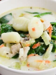 chicken gnocchi soup in a white bowl on table