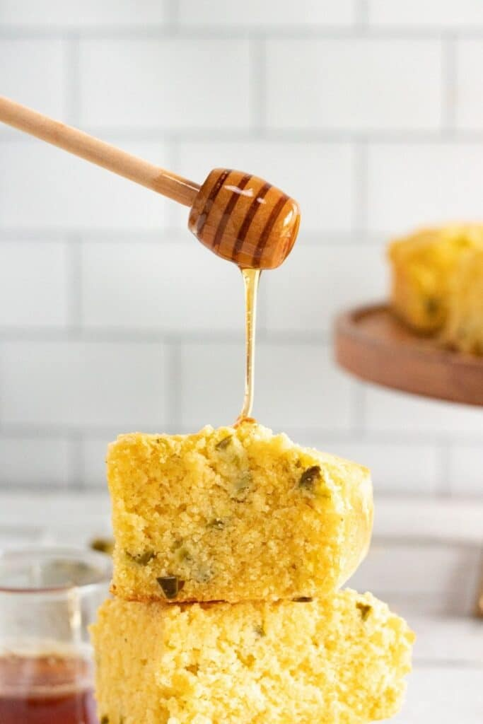 honey cornbread with honey getting drizzled on top