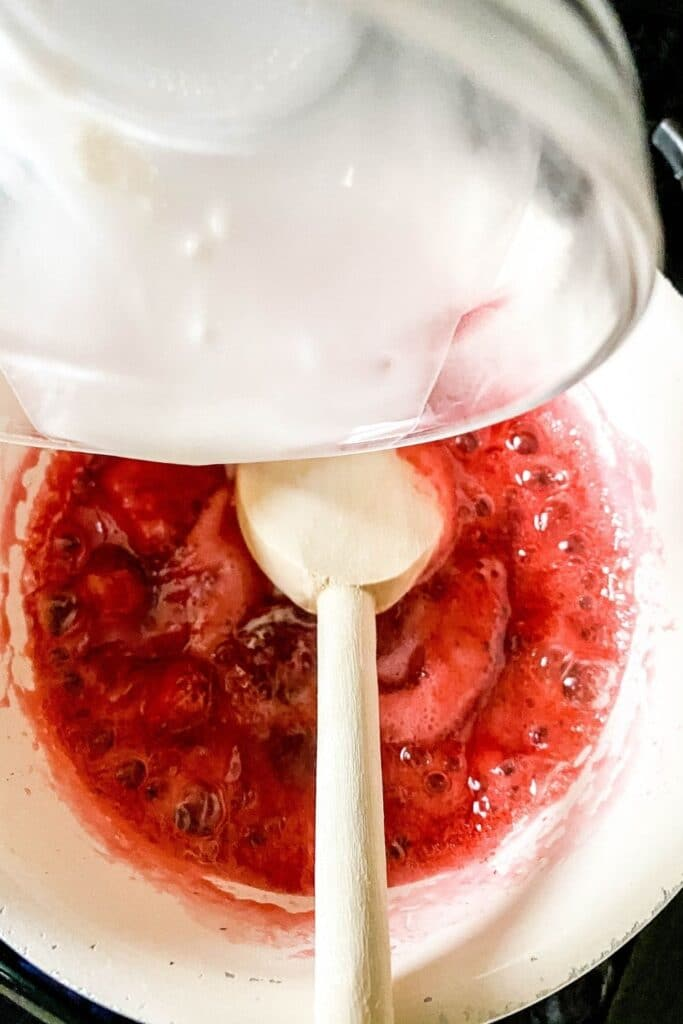 strawberry glaze in a pan getting thickened up with cornstarch slurry