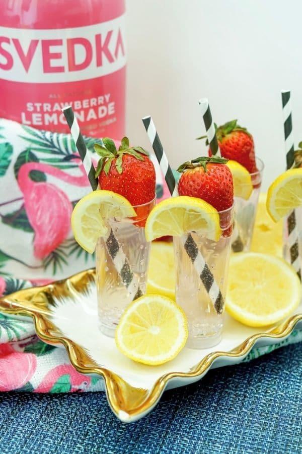 summer cocktails on a serving platter with vodka behind it