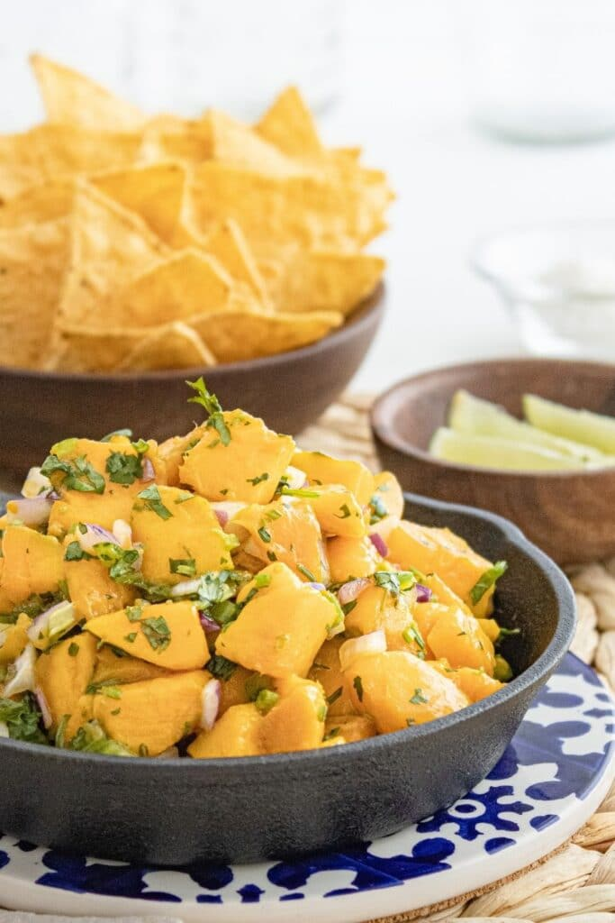 mango dish in pan with limes and chips by it