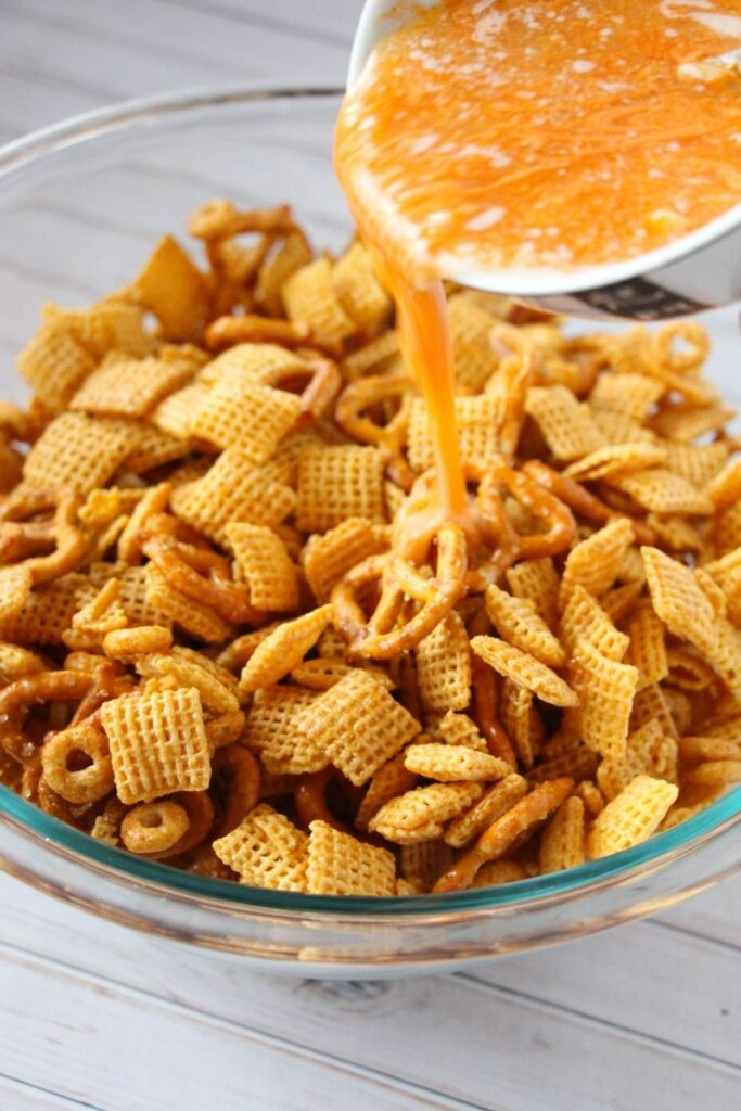 pouring butter and hot sauce on Chex mix