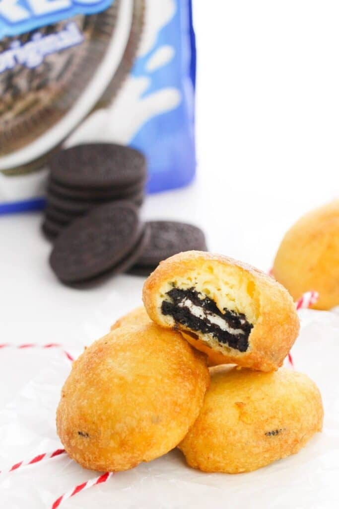 stack of deep fried Oreo cookies on table with Oreo container behind it