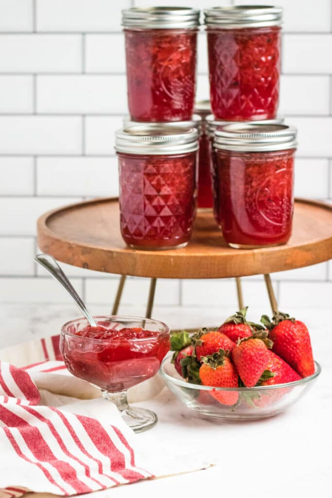 strawberry jam on counter with bowl of jam and berries