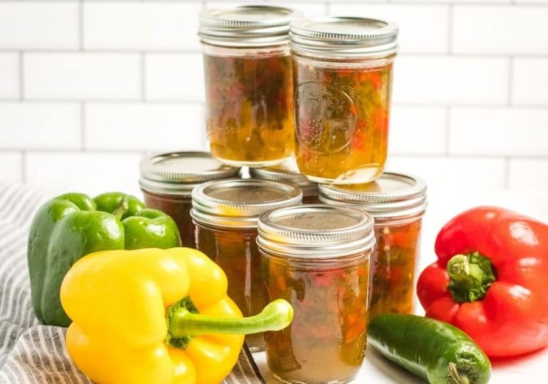 jars of pepper jelly with peppers around it