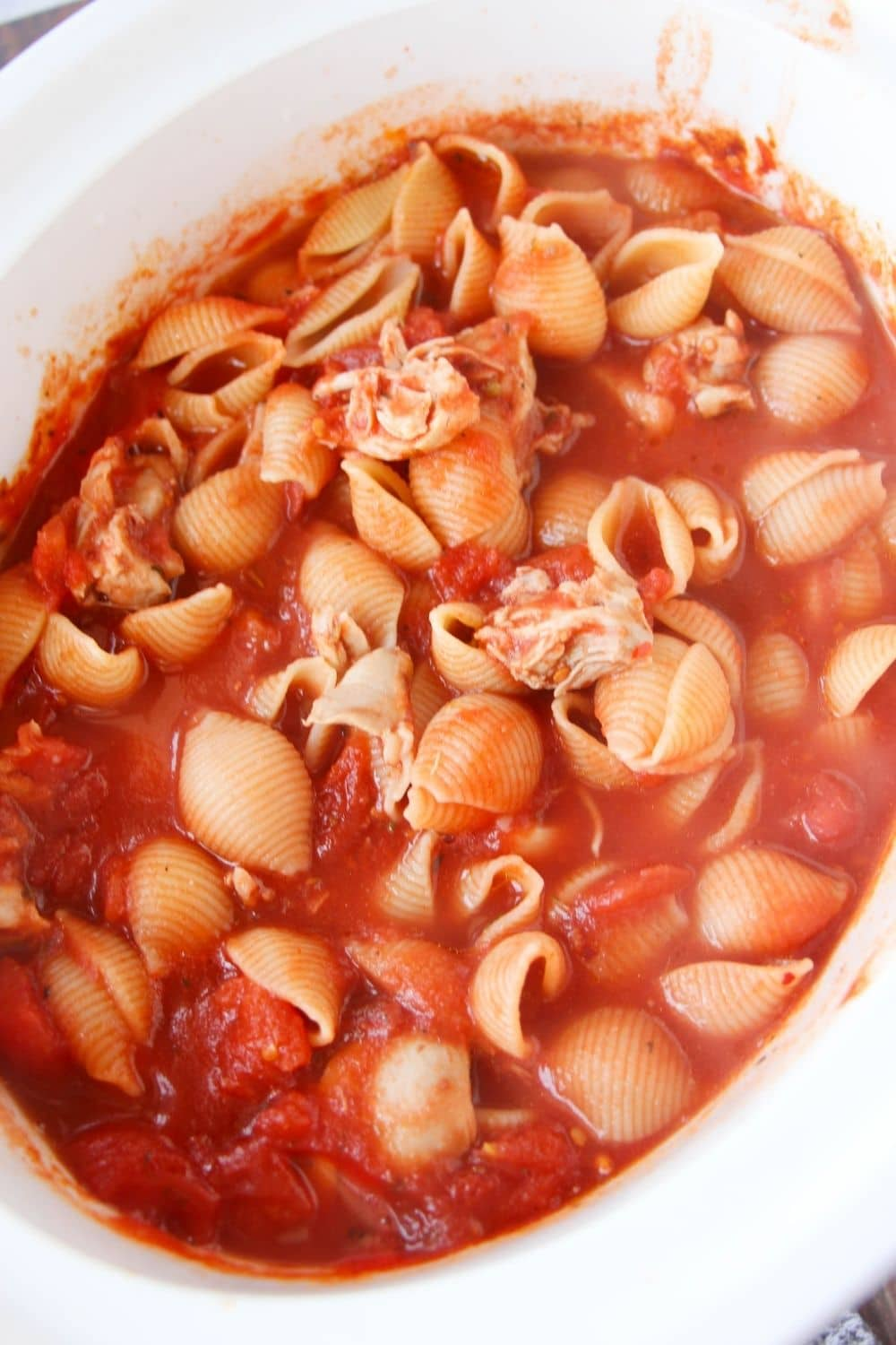dry pasta in crockpot with tomato sauce and chicken