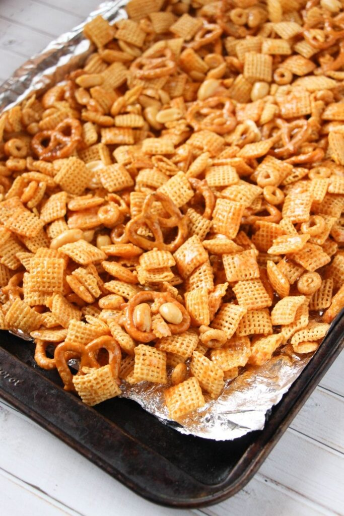 spicy snack mix on the baking sheet with aluminum foil