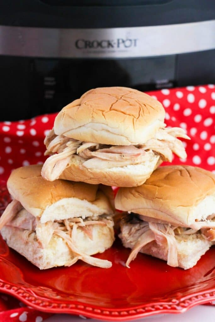 Red plate with slider chicken sandwiches stacked on it