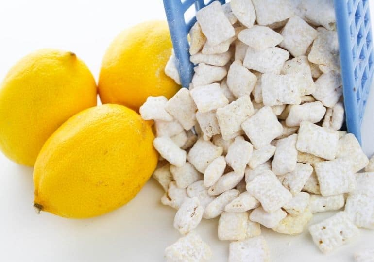 puppy chow coming out of a bowl with lemons beside it