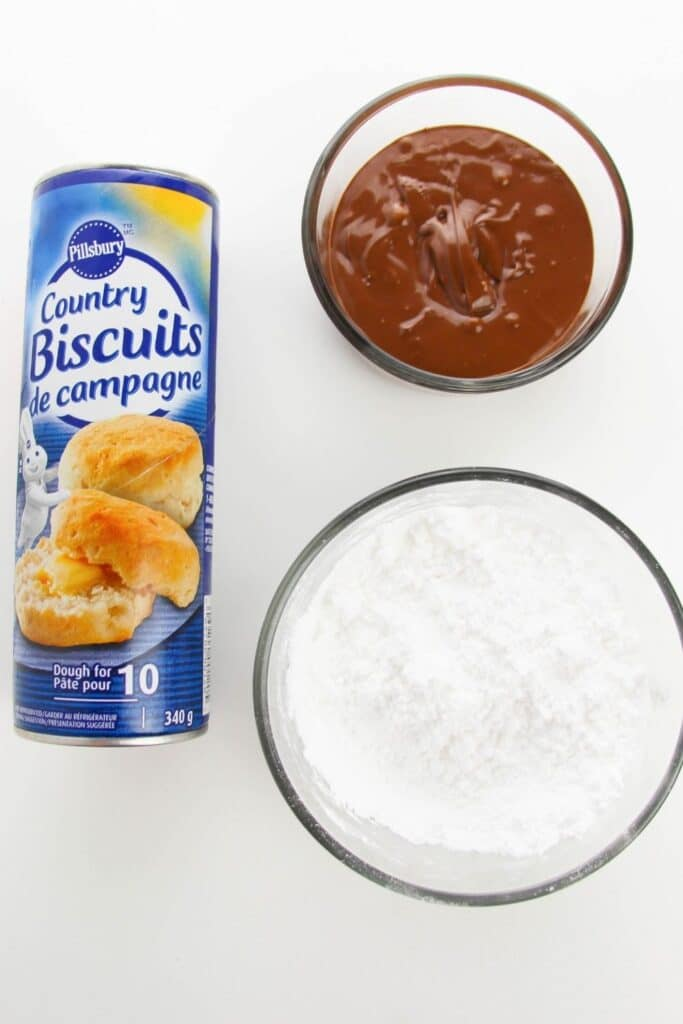 biscuits, nutella and powdered sugar on white counter