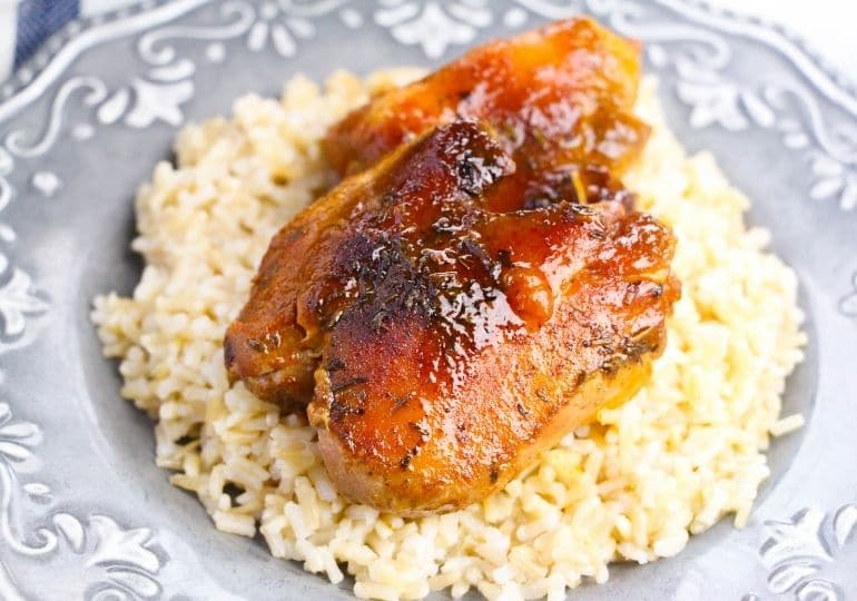 chicken thigh on plate with rice under it
