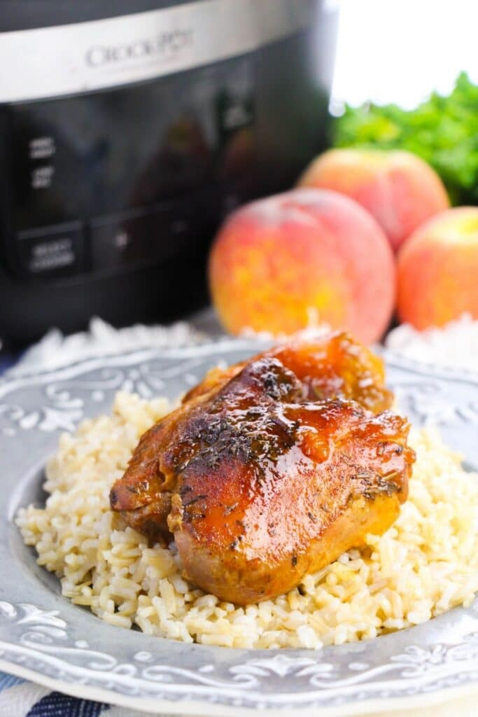 plate with rice and chicken on top and crockpot and peaches in background