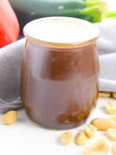 Kung Pao sauce in a jar with nuts around it