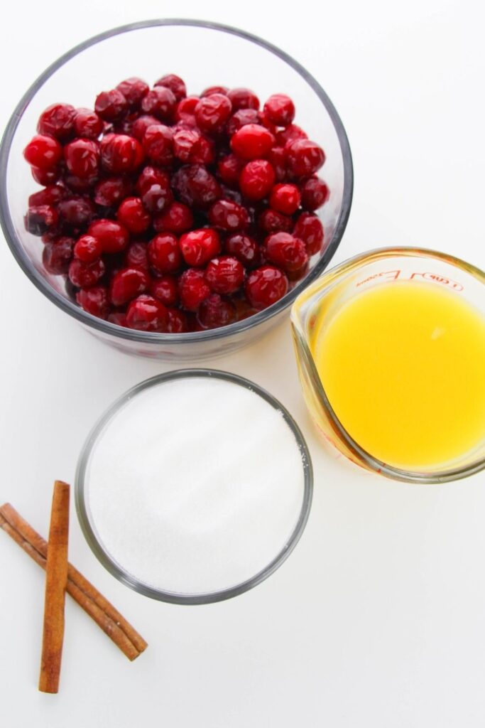 cranberries, juice, sugar and cinnamon sticks on white counter