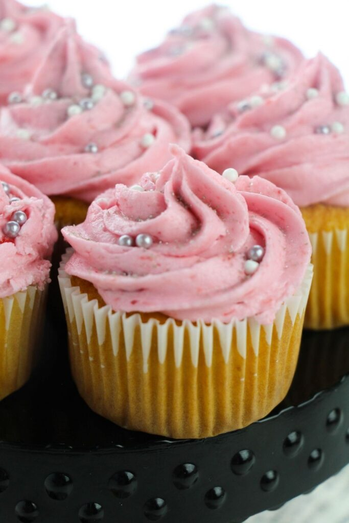 pink cupcakes with sprinkles on stand