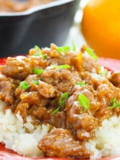 orange chicken on plate with rice and oranges in background