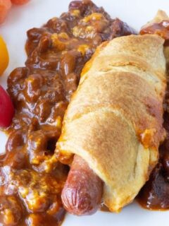chili cheese dog on plate with veggies