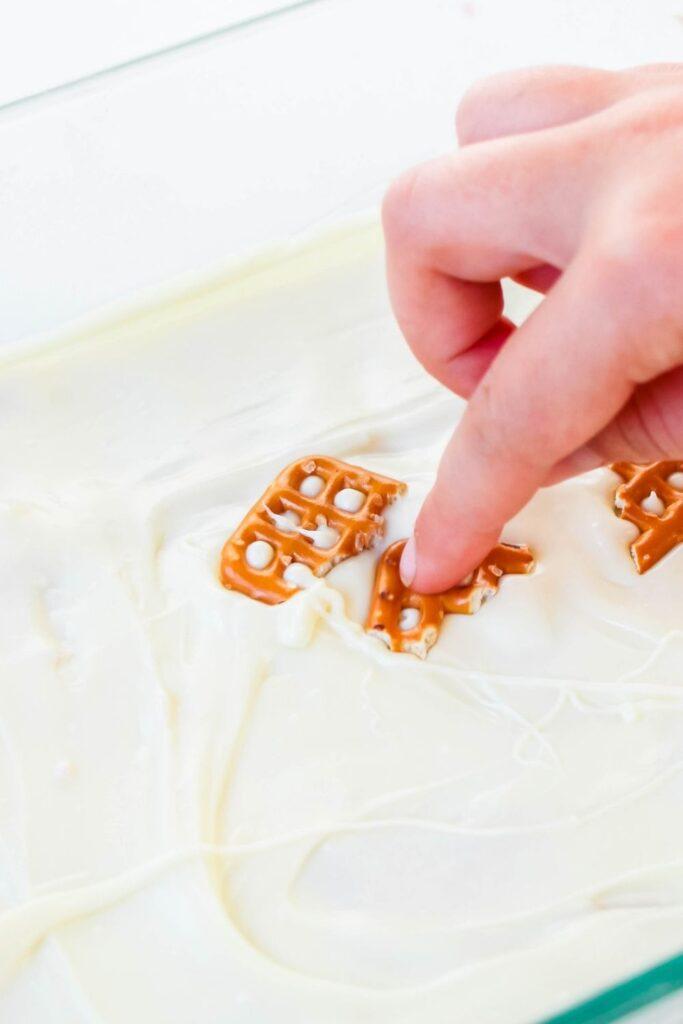 pressing pretzels into fudge