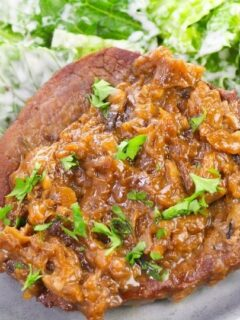 smothered steak on plate with salad